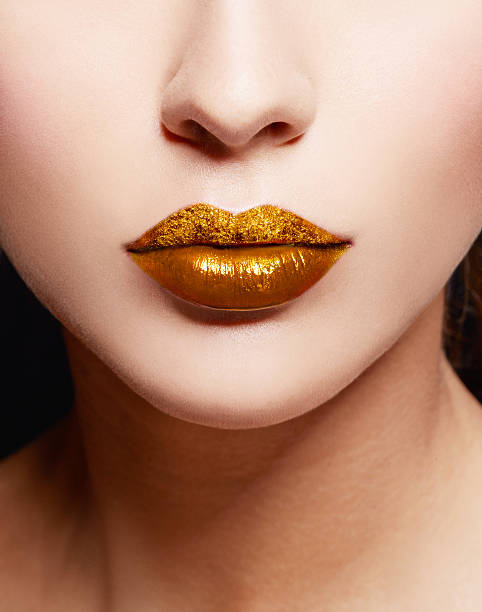 close up of gold artistic lips. makeup cosmetic image. - metallisches make up stock-fotos und bilder