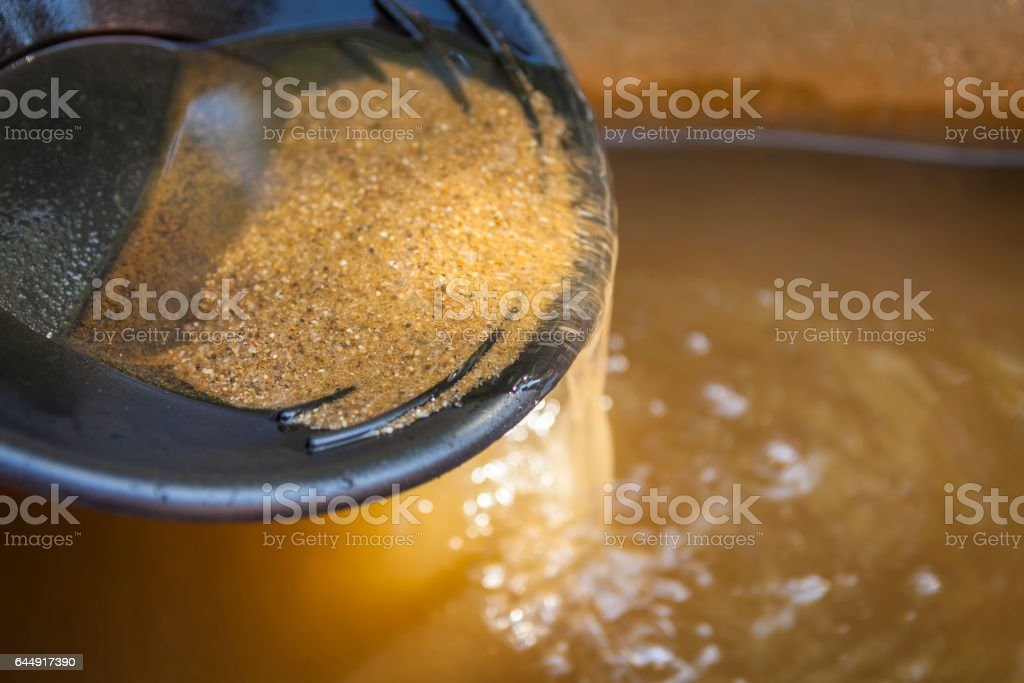 Close up of gold panning pan with sifting sand. Shallow depth of field with focus on sand flowing over edge of pan into water. stock photo