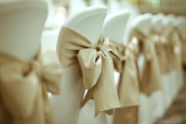 Nahaufnahme des goldenen Band gebunden weißen Stuhl in Luxus-Dinner-Party mit Vintage Farbstil. – Foto