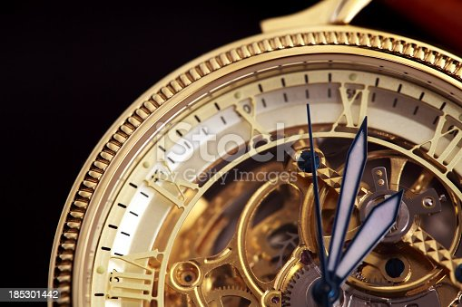 Golden wristwatch with a visible clockwork on black background