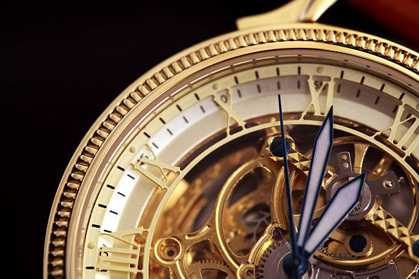 a close up of golden wristwatch with black hands - watch timepiece stock photos and pictures