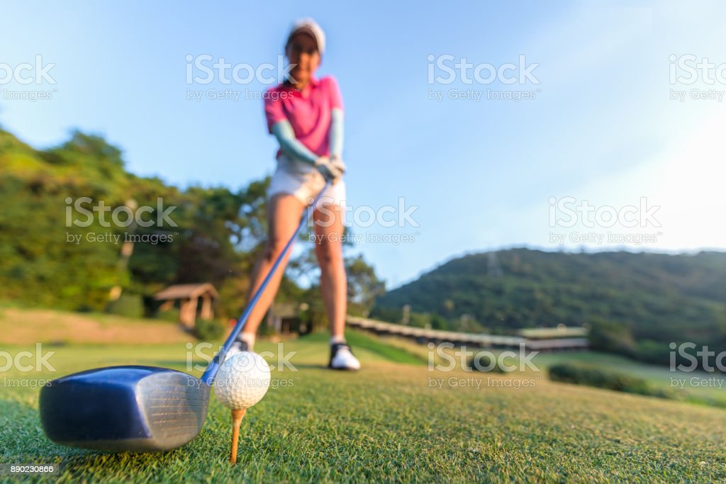 Close up of golf ball before a women tee off in the ground evening time.  Lifestyle Concept stock photo