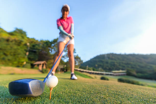 close up of golf ball before a women tee off in the ground evening time.  lifestyle concept - female golfer stock photos and pictures
