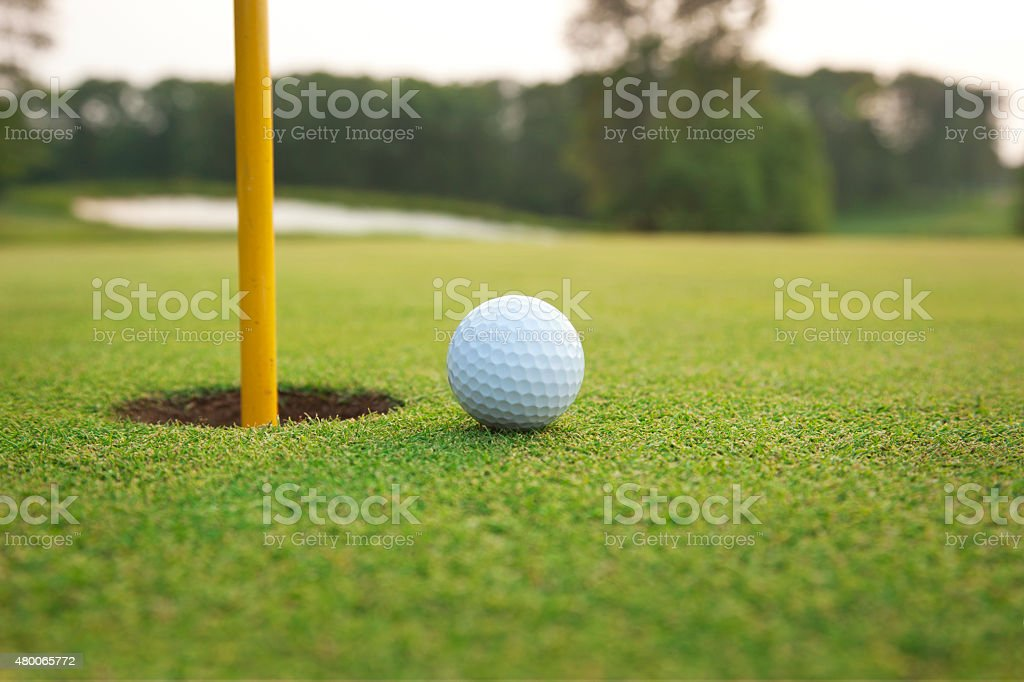 Close up of golf ball on a green near hole stock photo