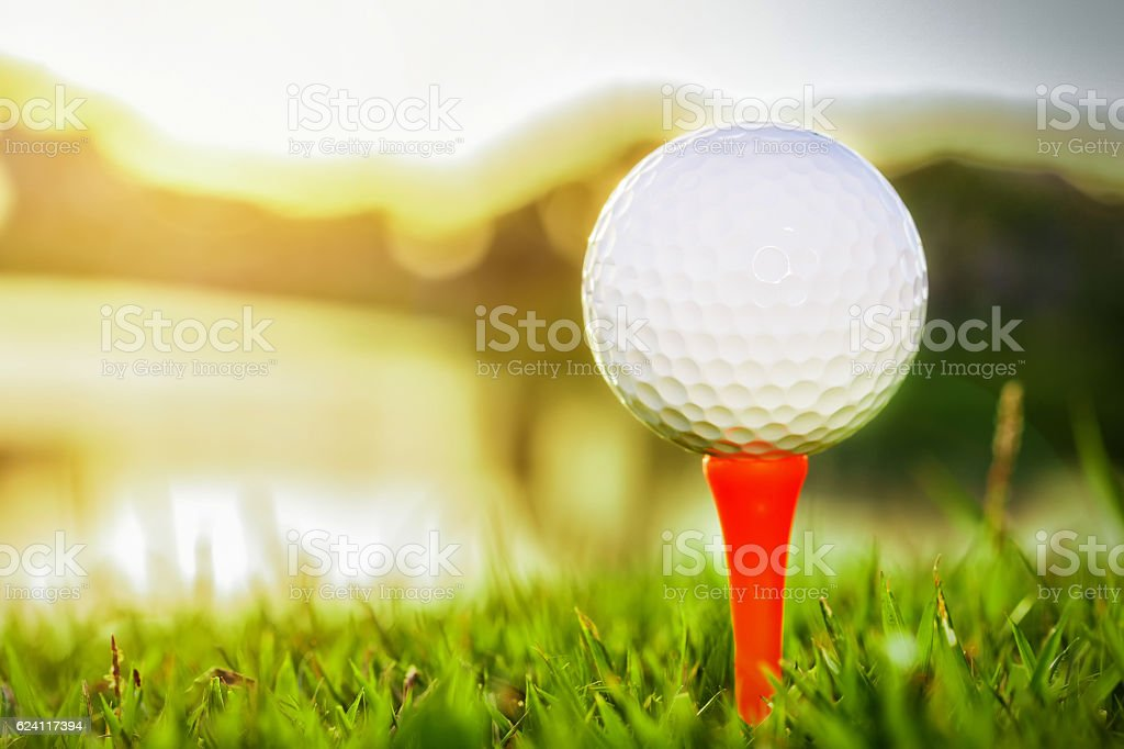 Close up of golf ball on tee against sunlight stock photo