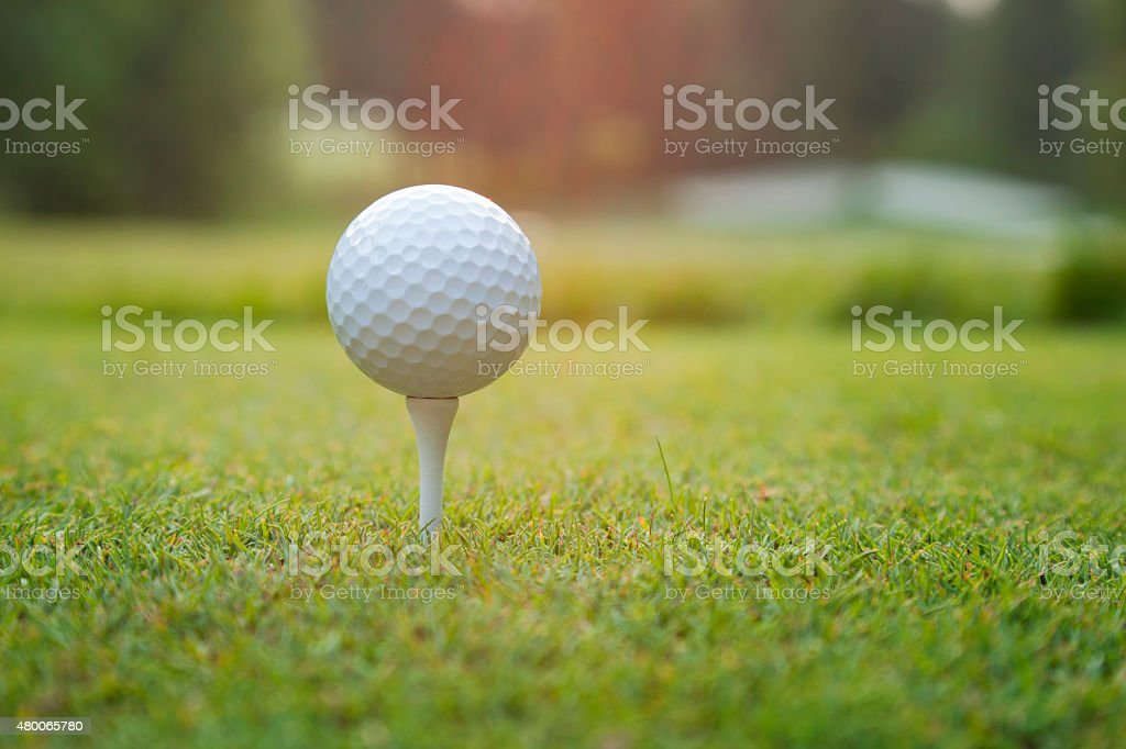 Close up of golf ball on tee at sundown stock photo