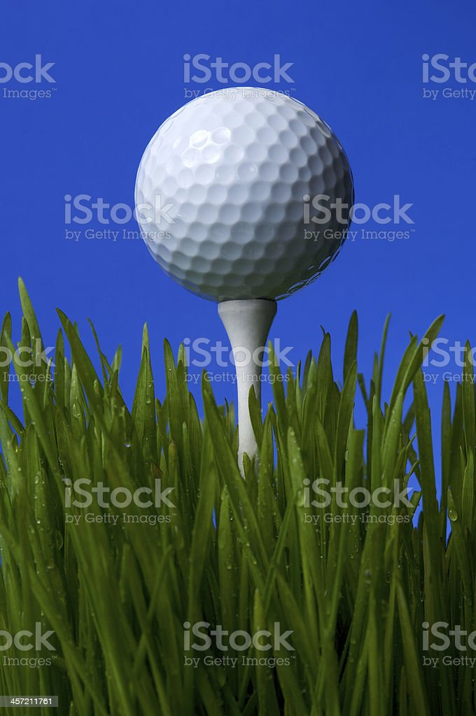 Close Up Of Golfball On Tee Against Blue Background Vertical royalty-free stock photo