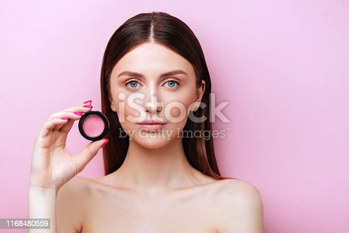 Close up of gorgeous charming lady with ideal face presenting new product.