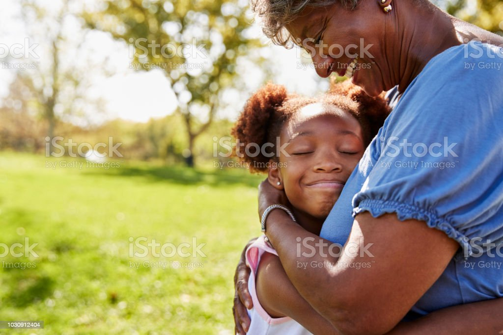 Close Up Of Granddaughter Hugging Grandmother In Park stock photo