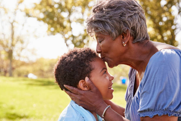Close Up Of Grandmother Kissing Grandson In Park stock photo