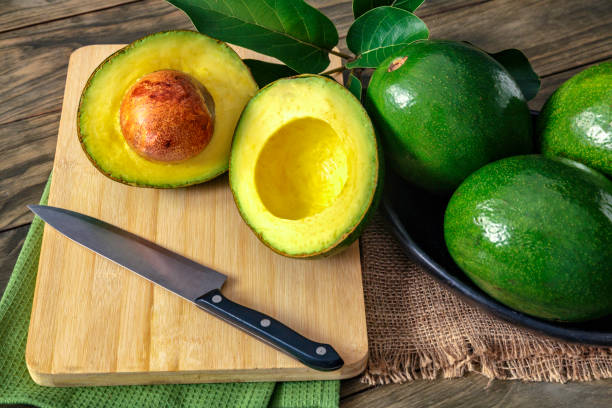Close up of green ripe avocados with leaves stock photo