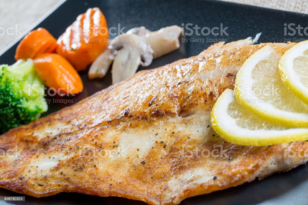 Close up of grilled fish with vegetables on a black plate stock photo