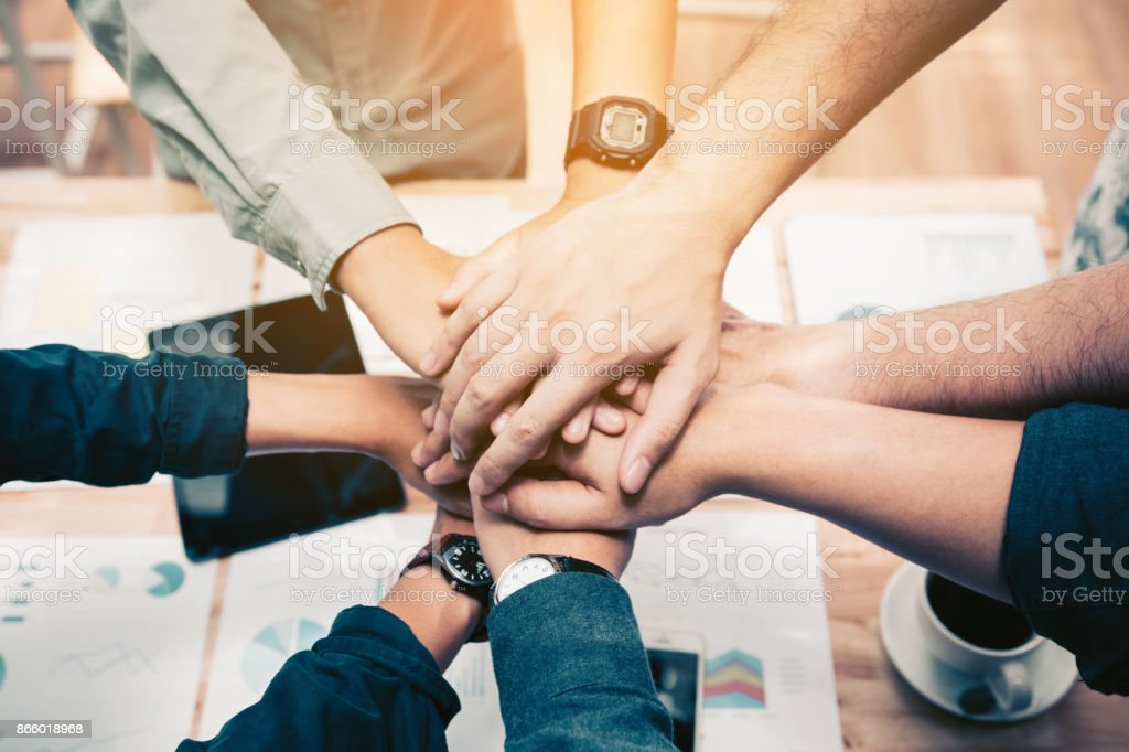 Close up of  group of business people joining their hands together in unity. stock photo