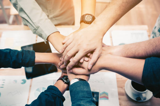 close up of  group of business people joining their hands together in unity. - dedication stock photos and pictures