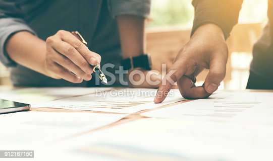 885956164istockphoto Close up of group start-up analysis to data paper chart on desk at working space. 912167150