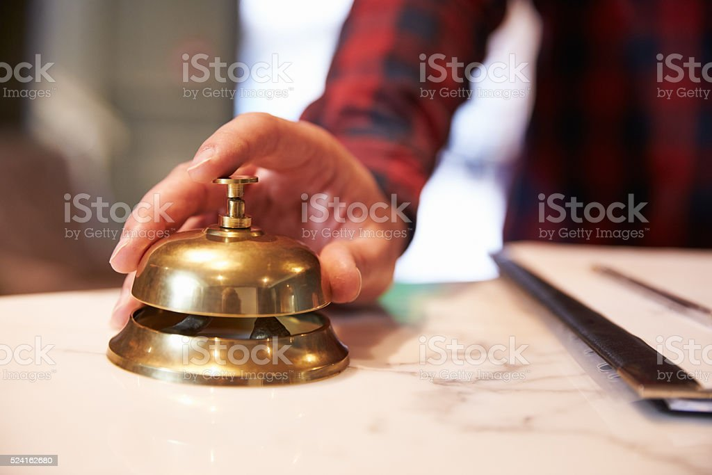 Close Up Of Guest's Hand On Hotel Reception Bell stock photo