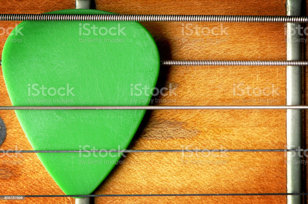 Close up of guitar pick and fretboard stock photo