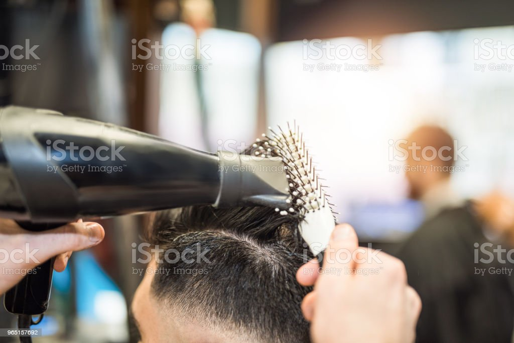 Close up of hair dresser drying client's freshly cut hair. royalty-free stock photo