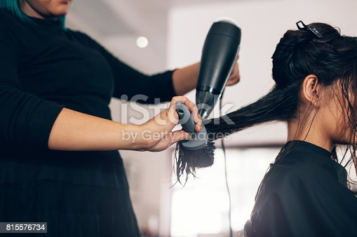 istock Close up of hair stylist using dryer on woman wet hair in salon 815576734