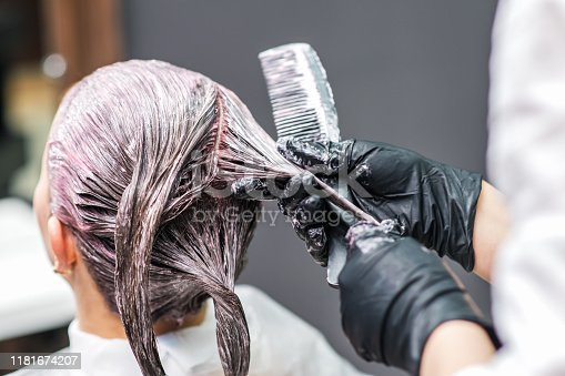 istock Close up of hairdresser hands is coloring woman's hair in black gloves. 1181674207