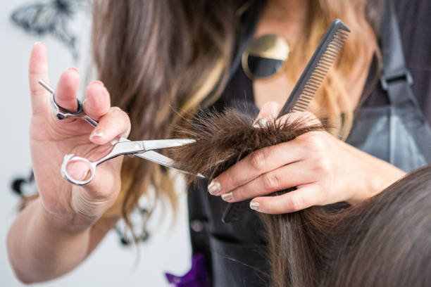 Close up of hairdressers hands cutting hair close up of a hairdressers hands cutting wet hair in a hair salon. hairstyle stock pictures, royalty-free photos & images