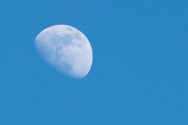 Close up of half moon during daylight with blue sky background, - image stock photo