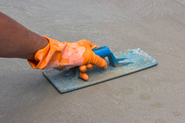 nahaufnahme von hand und nivellierung beton mit kelle - diy beton stock-fotos und bilder
