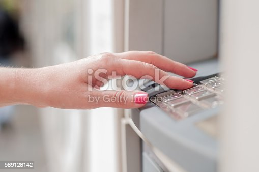 istock Close up of hand entering pin at an ATM. 589128142
