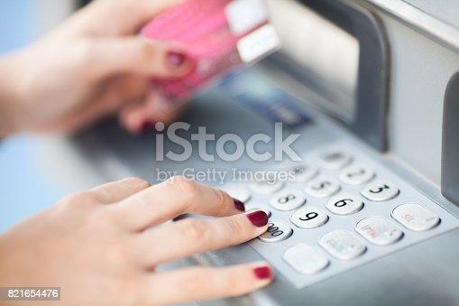 istock Close up of hand entering pin at an ATM 821654476
