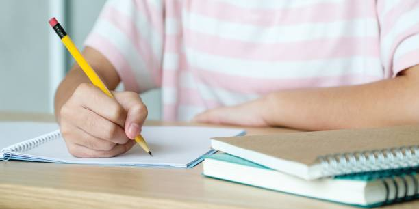 Close up of hand high school or university student in casual holding pencil writing on paper notebook, Teenager student hand writing lecture note book at school campus, College education stock photo