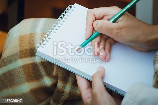 818512928istockphoto Close up of hand holding pencil and drawing in notebook. 1137026647