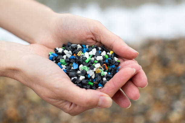 Close Up Of Hand Holding Plastic Granules Polluting Beach Close Up Of Hand Holding Plastic Granules Polluting Beach plastic pollution stock pictures, royalty-free photos & images