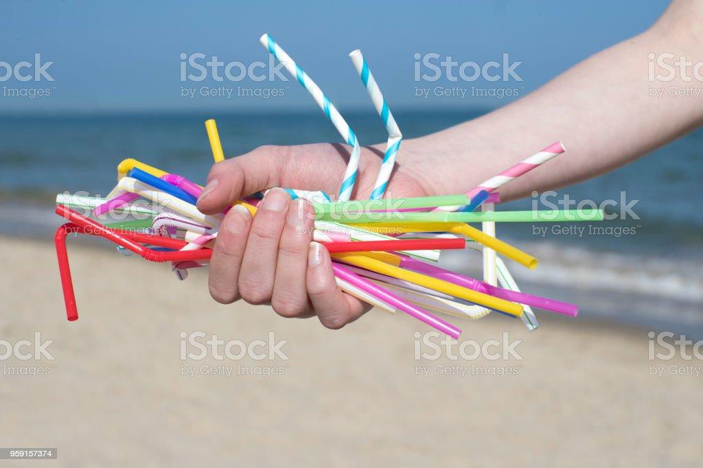 Close Up de la mano con Pajitas de plástico contaminan playa - Foto de stock de Adulto libre de derechos