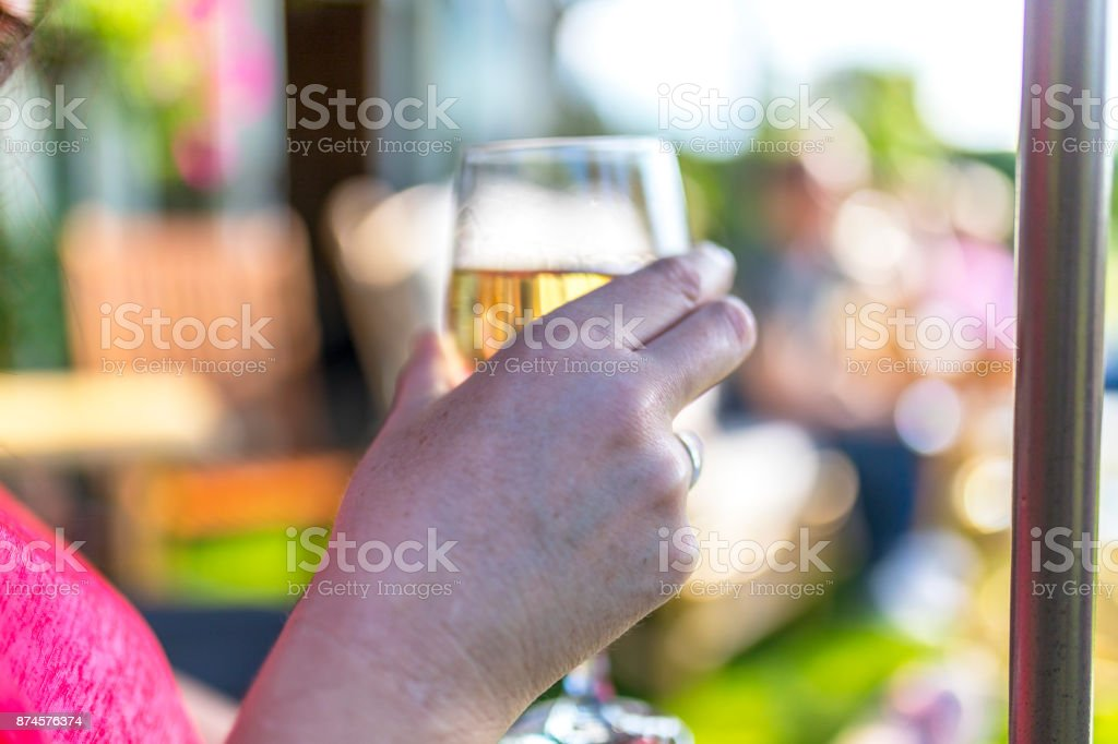 Close up of hand holding white wine glass at a summer get together in the UK stock photo