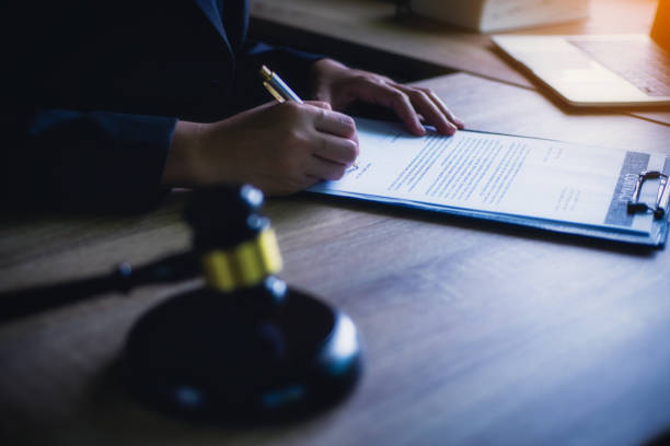 Close up of hand lawyer working signing contract paper with wooden gavel judge in the office. lawyer and law ,judiciary and legislature courtroom legal concept. stock photo