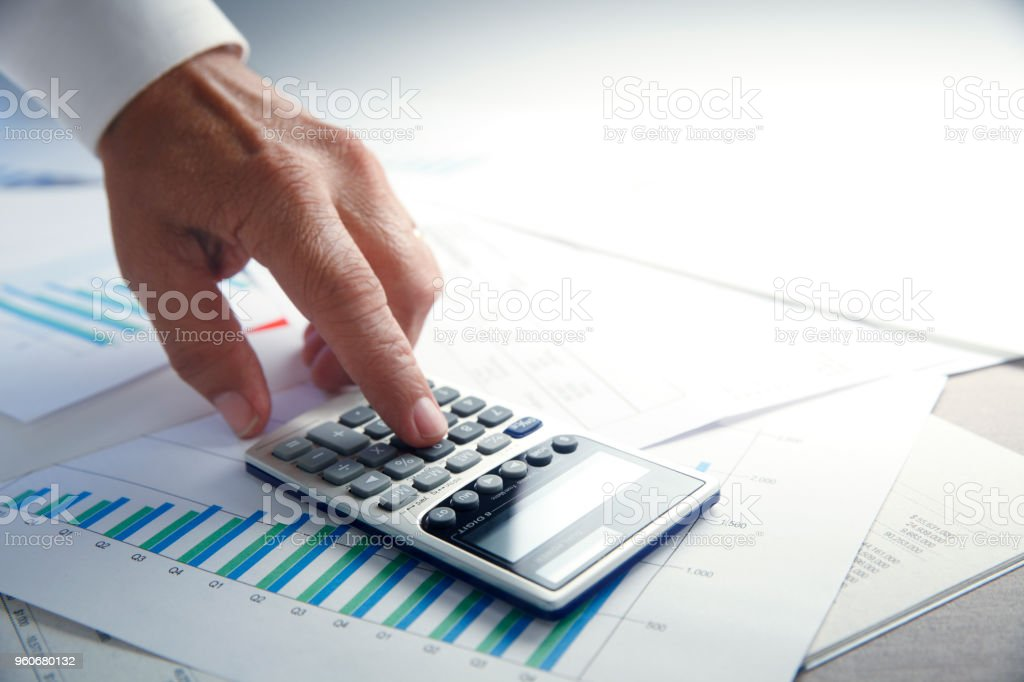 Close Up Of Hand Making A Calculation On A Calculator That Rests On Top Of Financial Chart stock photo