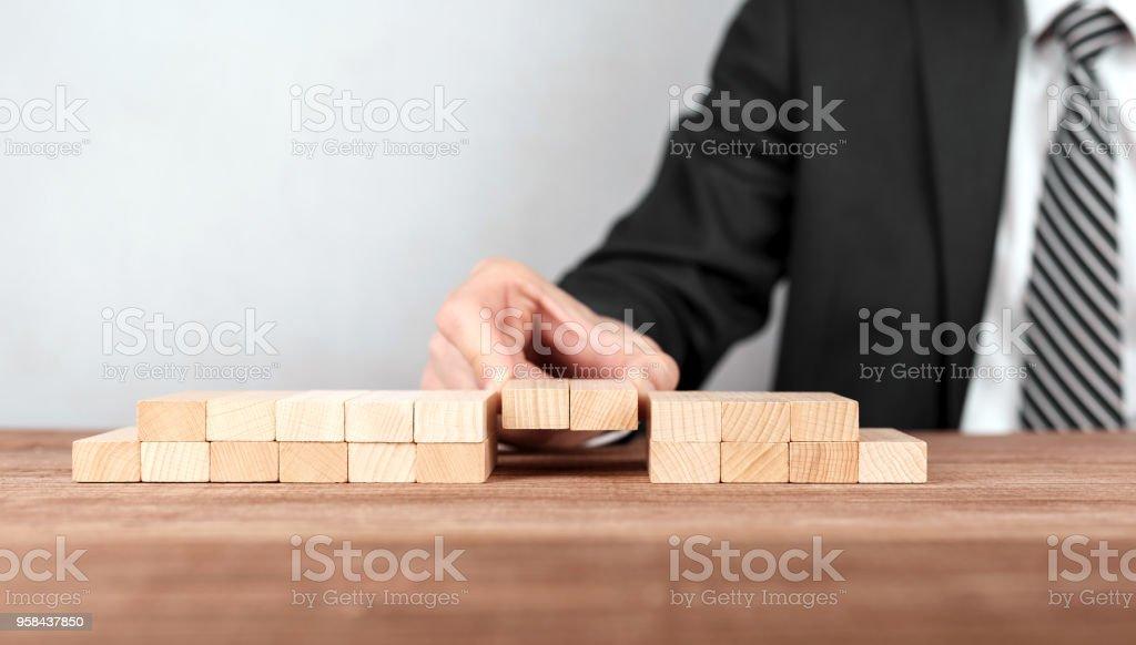 Close up of hand of businessman assembling a bridge made from little blocks. stock photo