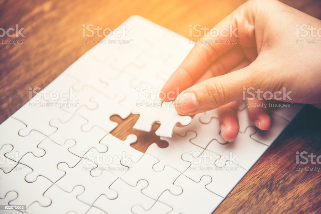 Close up of hand placing the last jigsaw puzzle piece, Hand holding missing jigsaw puzzle piece down in to the place, conceptual of problem solving, finding a solution. stock photo