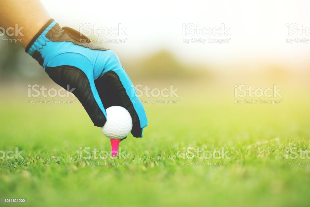 Close up of Hand putting golf ball on tee in golf course on...