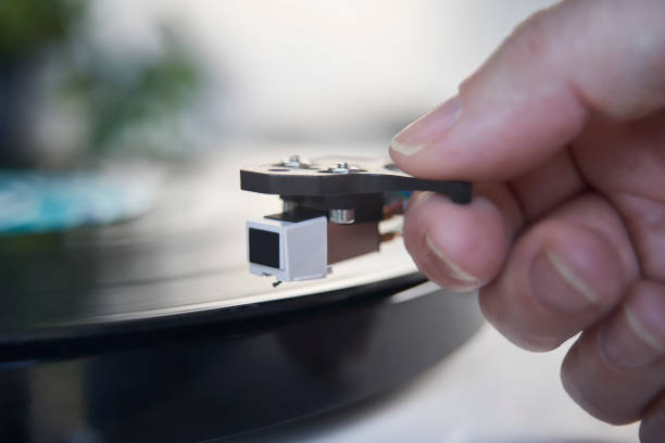Close Up Of Hand Putting Needle Of Record Player Turntable On Vinyl LP stock photo