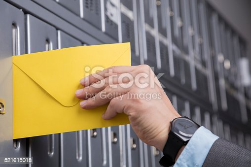 istock Close up of hand putting the yellow letter into the mailbox 521615018