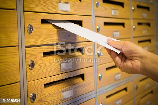 istock Close up of hand putting the yellow letter into the mailbox 545085804