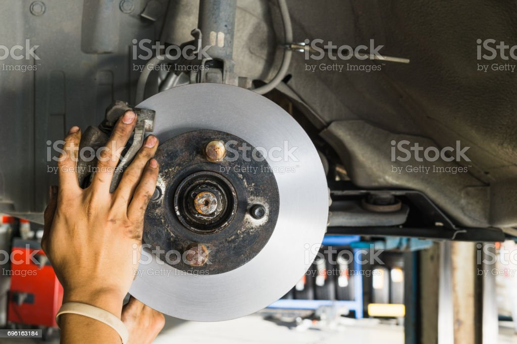 close up of hand replacing a new disc brakes stock photo