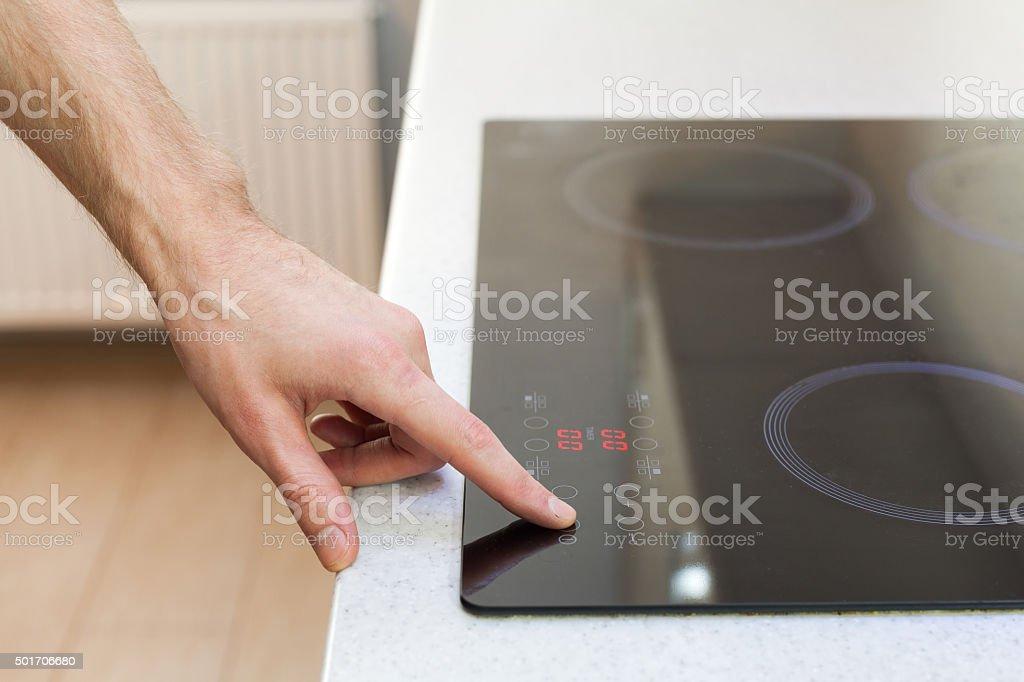 Close Up Of Hand Turning On Ceramic Stove stock photo