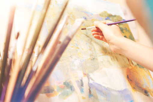 577949148 istock photo Close up of hand with brush working on abstract picture 854027160