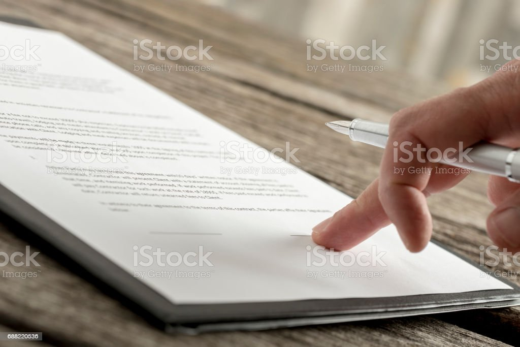 Close up of hand with fancy pen on document stock photo