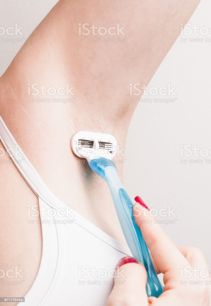 Close up of hand woman shaves armpit disposable razor. Armpit's care concept. stock photo