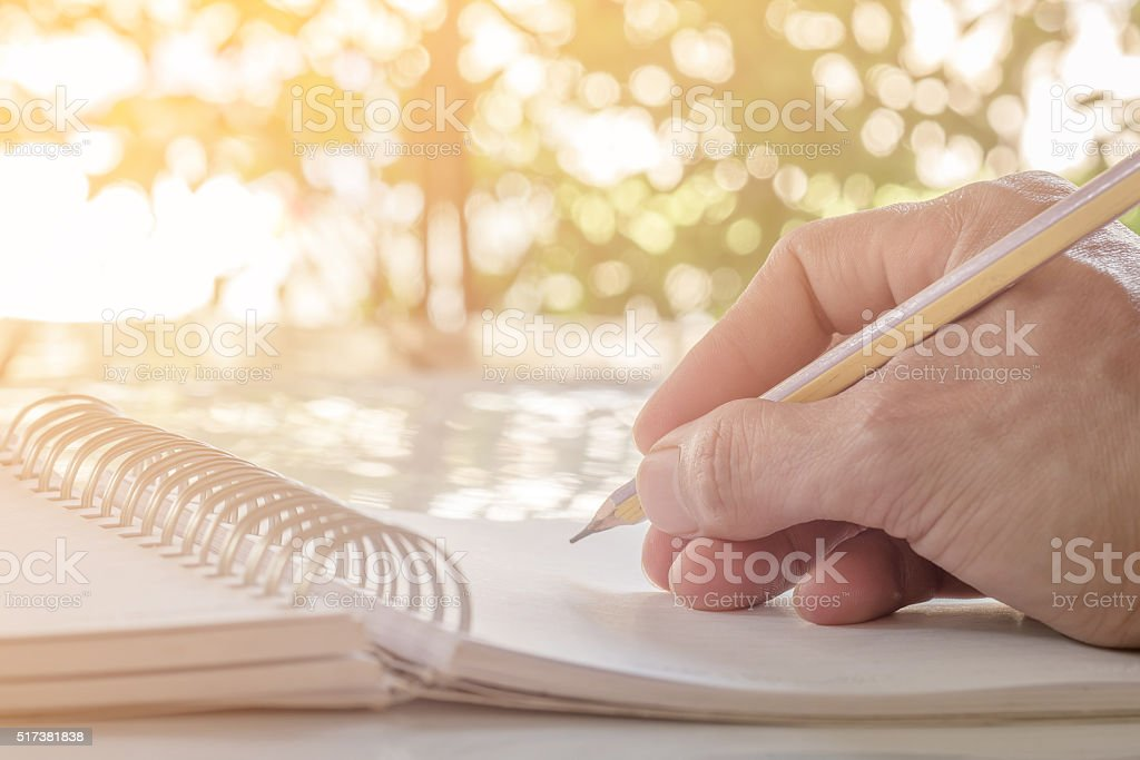 Close up of hand writing on notebook with pencil
