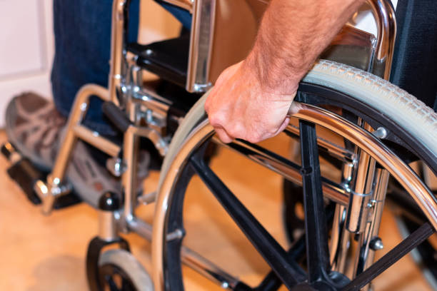 Close up of handicapped man's hand pushing wheel of wheelchair stock photo
