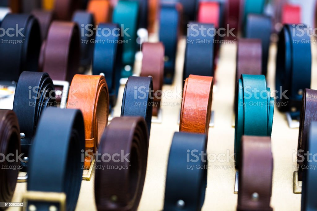 Close up of handmade multi colored leather belts in a row for sale at market, London, UK stock photo